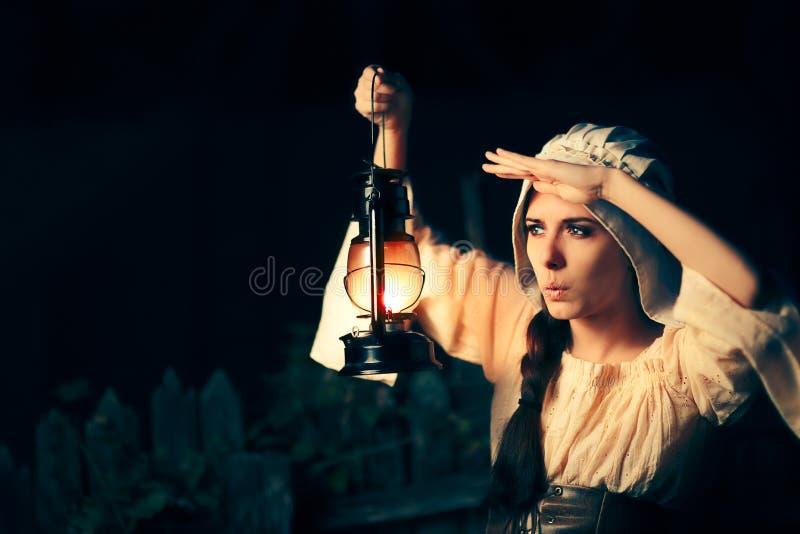 有外面葡萄酒灯笼的好奇中世纪妇女在晚上 免版税库存照片