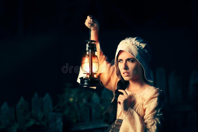 有外面葡萄酒灯笼的好奇中世纪妇女在晚上 库存图片