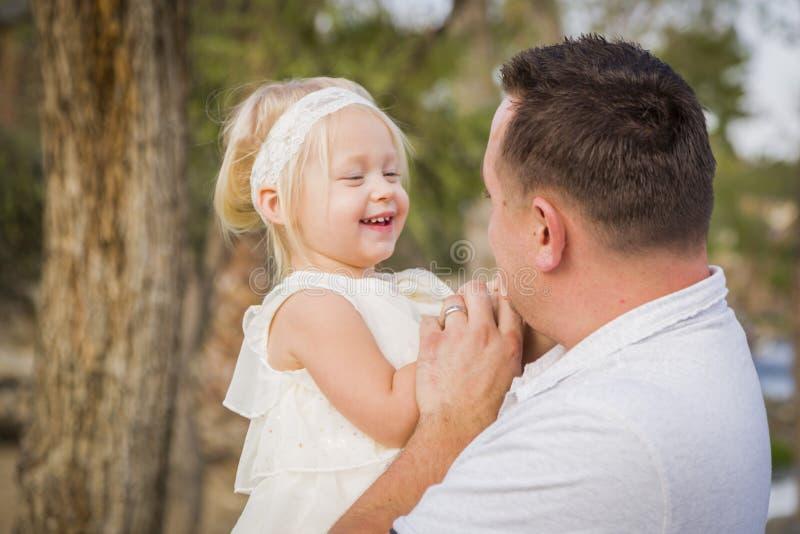 有外面逗人喜爱的女婴的嬉戏的父亲在公园 库存照片