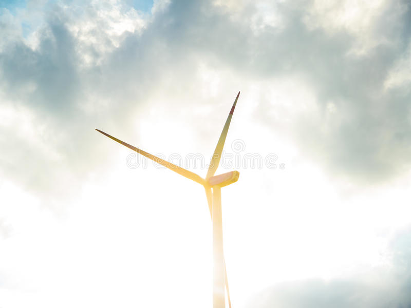 有多云天空和太阳的风轮机 免版税库存图片