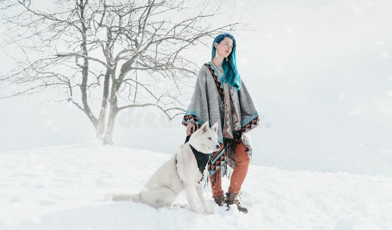 有多壳的狗的美丽的妇女在冬天 库存照片