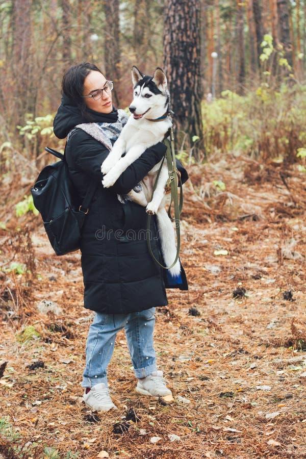 有多壳的狗的美丽的年轻女人 免版税库存图片