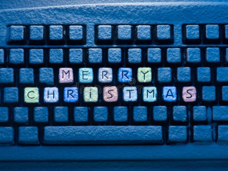 有多彩多姿的文本圣诞快乐的键盘在按钮上用雪盖照亮由蓝色霓虹灯 免版税库存图片