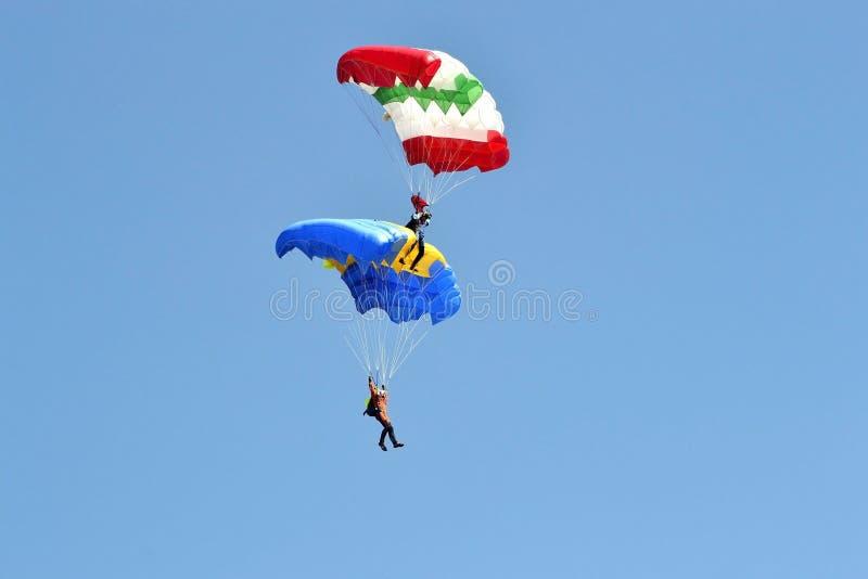 有多彩多姿的降伞的两个飞将军在天空飞行 免版税库存照片