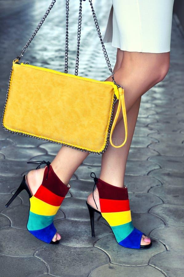 有多彩多姿的鞋子的妇女腿有高跟鞋和黄色袋子的 库存图片