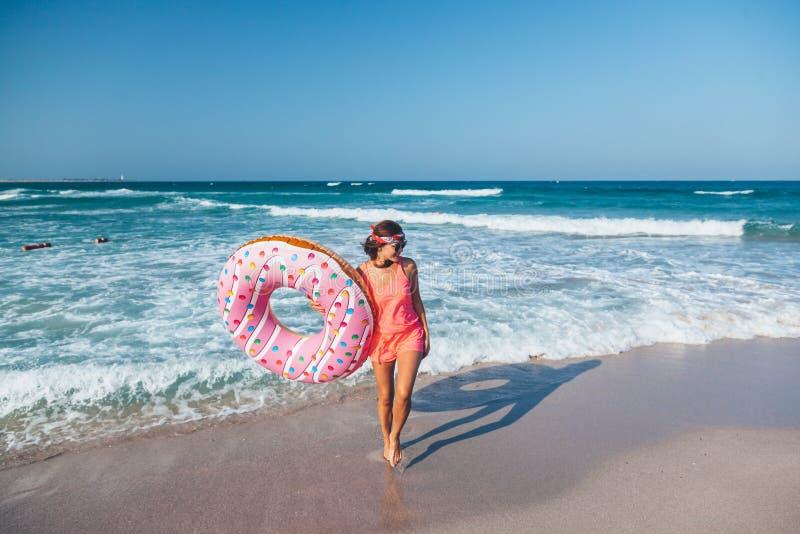 有多福饼lilo的女孩在海滩 免版税库存图片