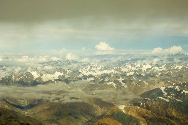 有多雪的山和峰顶的黄色灰色沙漠山谷在从了不起的高度的白色云彩下 免版税库存照片