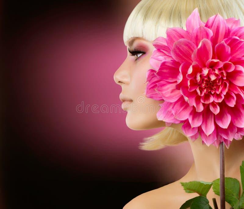 有大丽花花的白肤金发的妇女 免版税库存照片