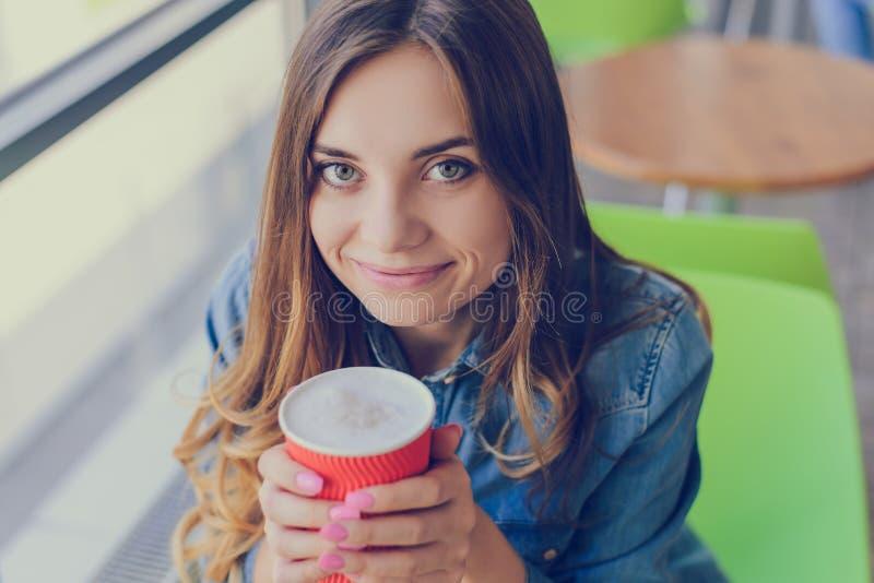 有大举行一个杯子可口c的眼睛和迷人的微笑的美丽的微笑的快乐的激动的愉快的好高兴的逗人喜爱的可爱的妇女 免版税库存照片