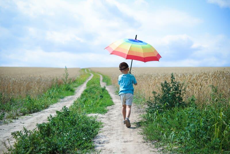 有大伞的走开的小男孩  图库摄影