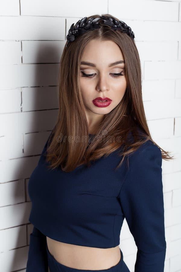 有大充分的嘴唇有明亮的晚上构成的和深红唇膏的时兴的美丽的性感的女孩在她的有花圈的嘴唇  免版税库存照片