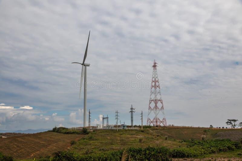 有大功率塔的风轮机和在山的高压次级驻地 库存图片