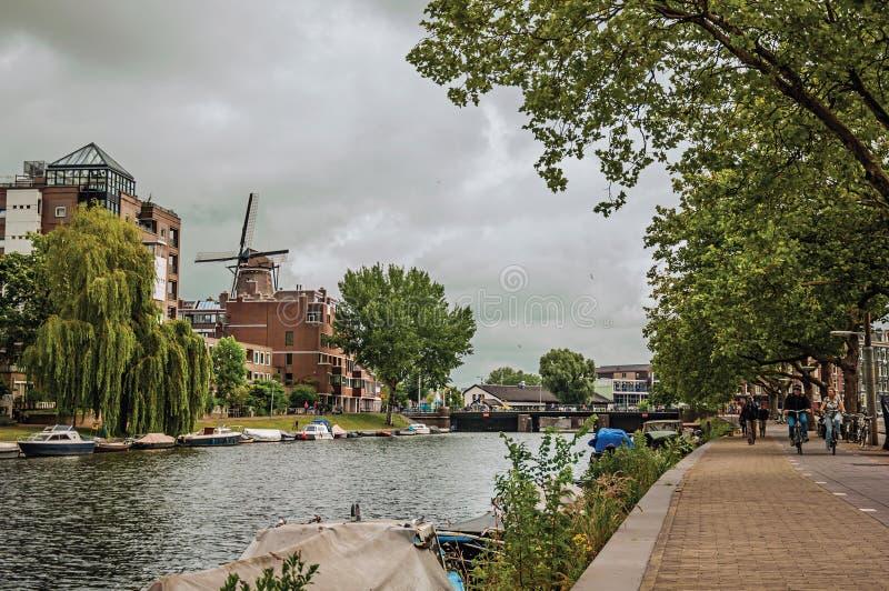 有大厦、被停泊的小船、骑自行车者和多云天空的树木繁茂的运河在阿姆斯特丹 免版税库存图片