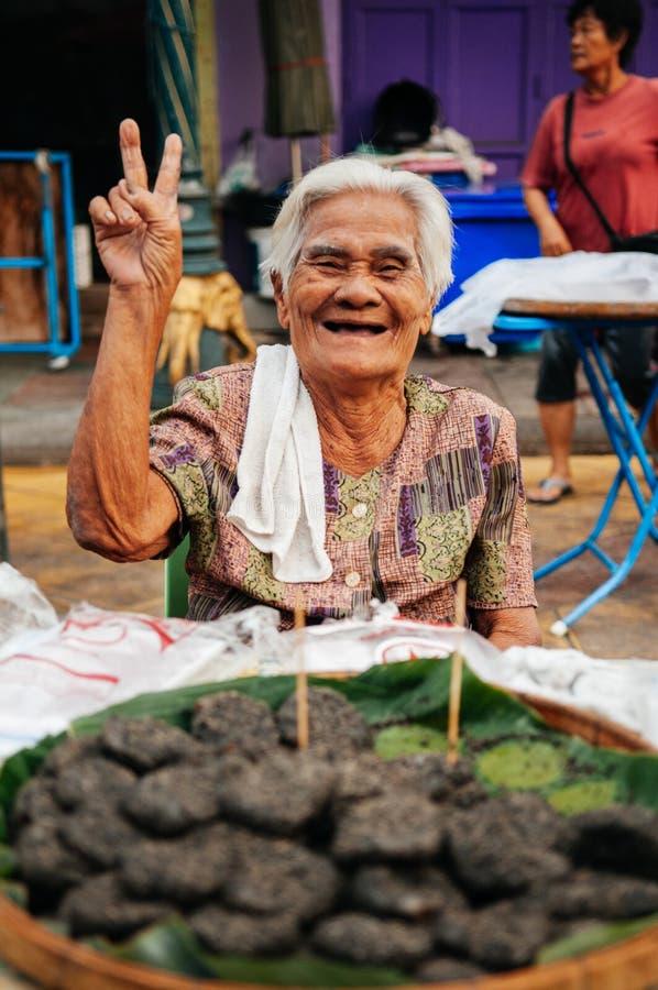 有大受欢迎的微笑的泰国老婆婆在地方市场卖泰国 库存图片