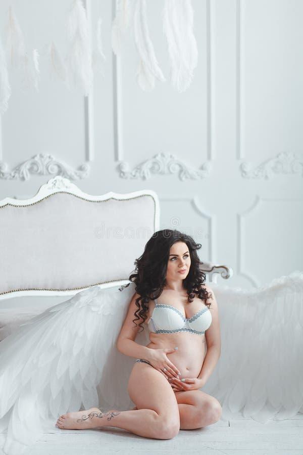 有大天使的美丽的年轻怀孕的女孩在白色演播室飞过 坐在葡萄酒沙发附近的地板 库存图片