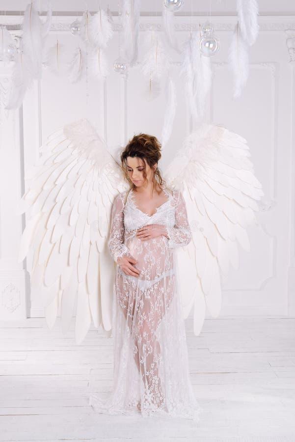 有大天使的美丽的年轻怀孕的女孩飞过 库存照片