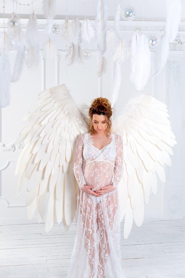 有大天使的美丽的年轻怀孕的女孩飞过 图库摄影