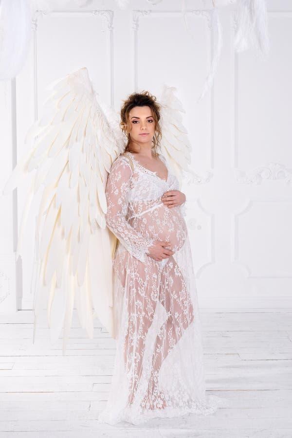 有大天使的美丽的年轻怀孕的女孩飞过 免版税库存照片
