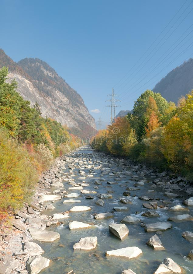 有大岩石和秋天颜色森林的山与格子十字架的河在瑞士和输电线 免版税图库摄影
