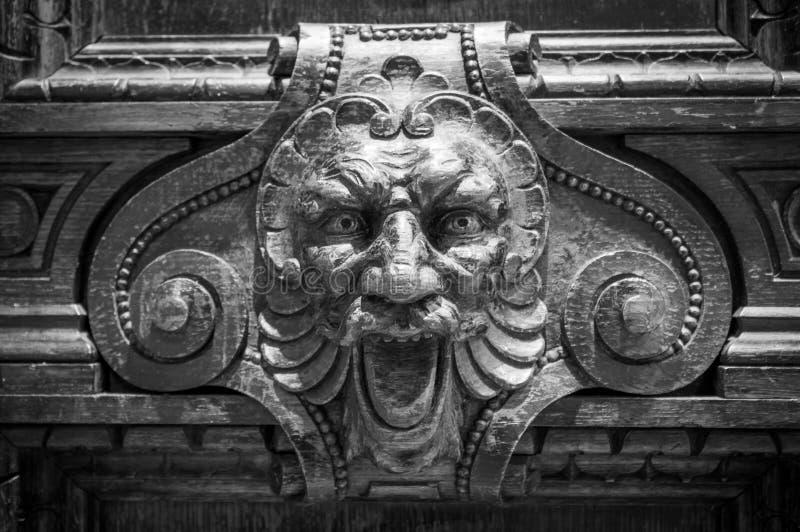 有大开的嘴的灰色石狮子头 另一牙丢失 雕塑的细节,关闭照片 库存图片