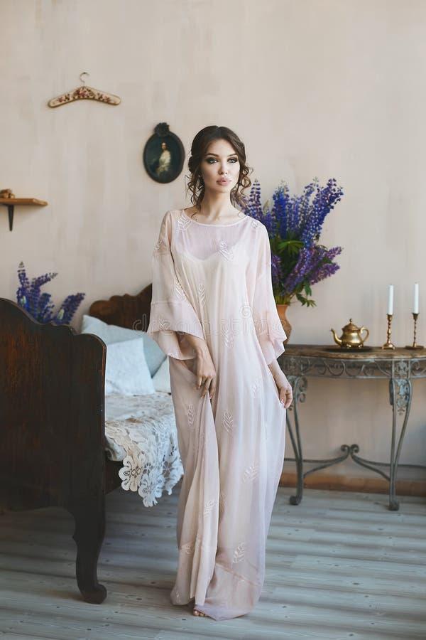 有大性感的嘴唇的美丽和肉欲的深色的式样女孩在摆在古色古香的床附近的灰色时兴的礼服在 免版税库存图片