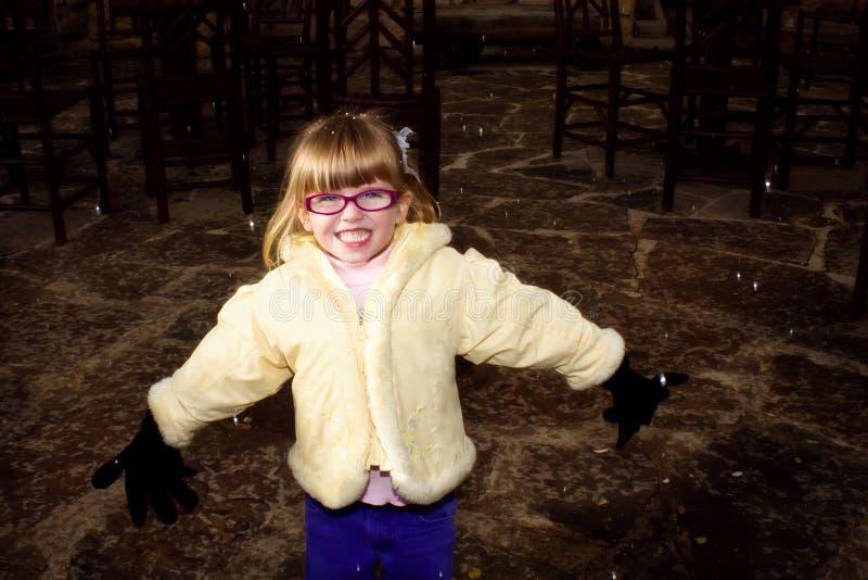 有大手套的愉快的女孩在新的落的雪 库存图片
