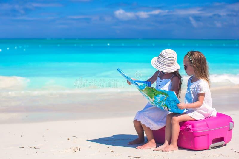 有大手提箱和一张地图的小逗人喜爱的女孩在热带海滩 库存图片