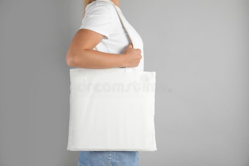 有大手提袋的妇女在灰色背景 库存照片