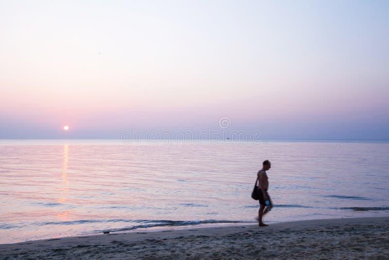 有大手提袋的赤足走在海滩的身份不明的胸部赤裸的人画象在日落 r r 免版税库存照片