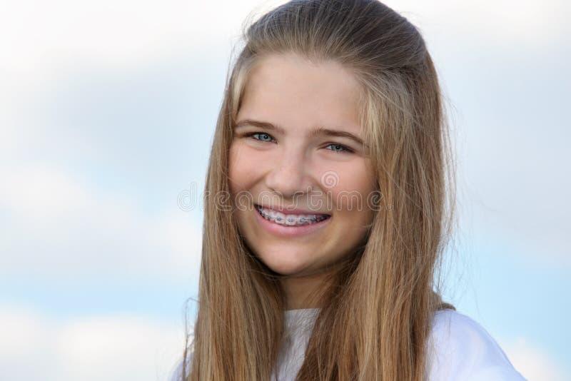 有大括号微笑的美丽的女孩 免版税图库摄影
