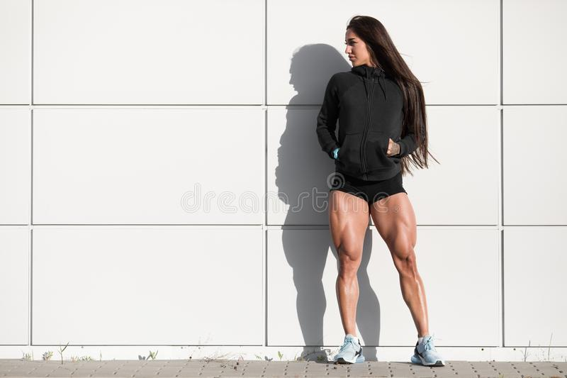 有大方形字体的性感的运动妇女 摆在室外,肌肉腿的肌肉女孩 免版税库存图片