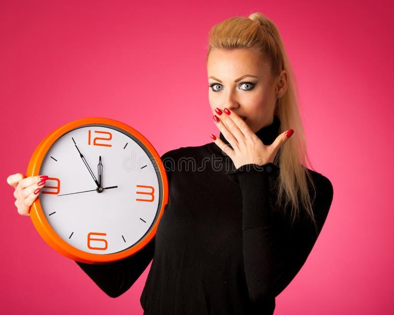 有大橙色时钟的担心的妇女打手势延迟,仓促, nervo的 免版税库存图片