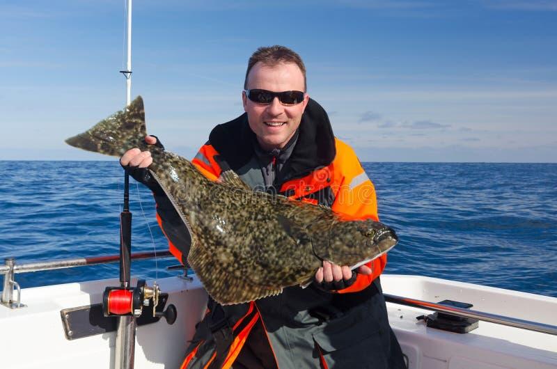 有大比目鱼鱼的愉快的钓鱼者 库存图片