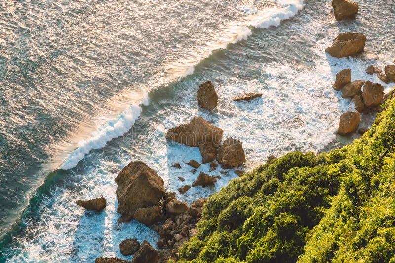 有大波浪、岩石和峭壁的海洋在温暖的日落的Uluwatu 库存照片