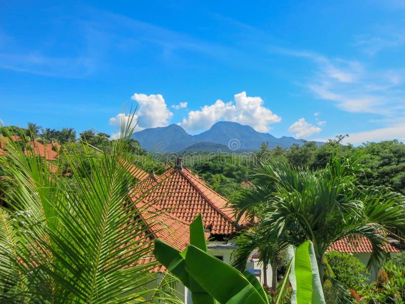 有大游泳场的热带装饰庭院 水表面上的反射 在背景中Lempuyang山  免版税库存图片
