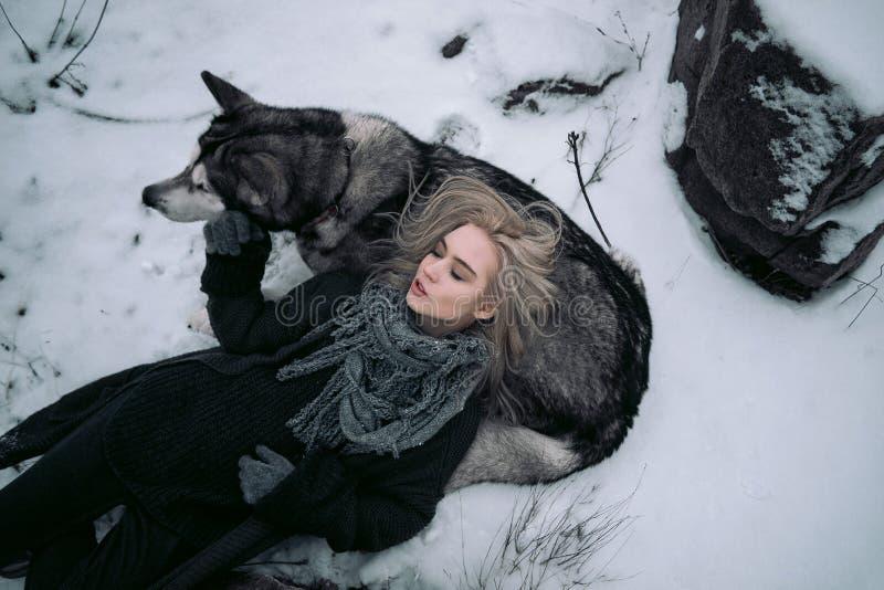 有大爱斯基摩狗狗的女孩在冬天背景 库存照片