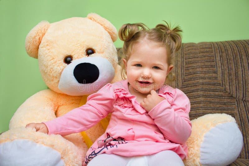 有大玩具熊的小女孩坐沙发在客厅 库存照片