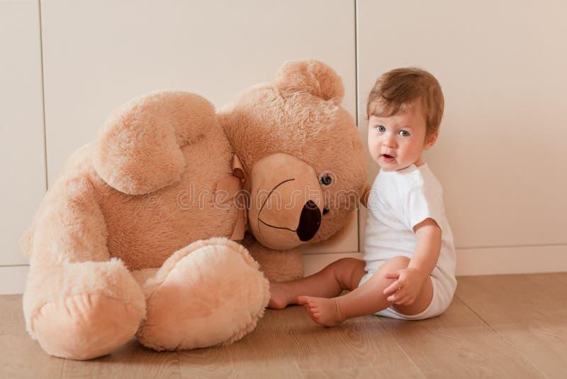 有大玩具熊的逗人喜爱的矮小的男婴 库存照片