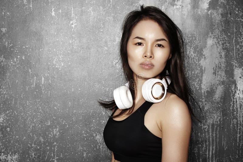 有大白色耳机的美丽的体育妇女 式样听音乐 健身画象,完善的身体形状 图库摄影