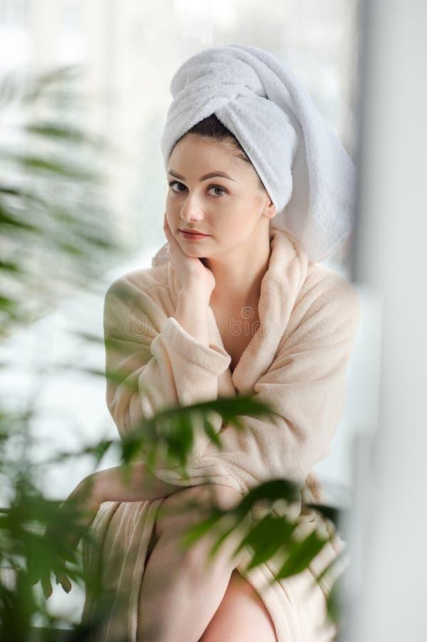 有大眼睛和黑暗的眼眉的少女,在顶头轻的裸体构成的白色毛巾,秀丽照片 免版税库存图片