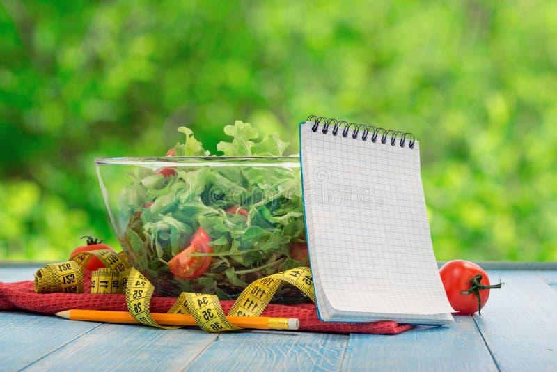 有大碗的空白的笔记本沙拉和测量的磁带 免版税库存图片
