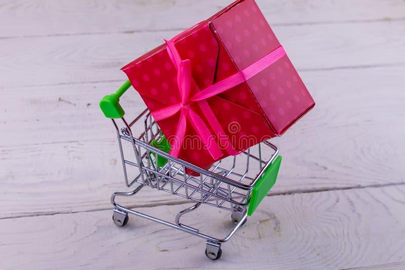 有大礼物盒的手推车在白色木背景 免版税库存照片
