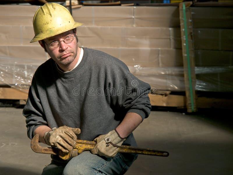 有大管扳手的男性建筑工人在膝盖 库存照片