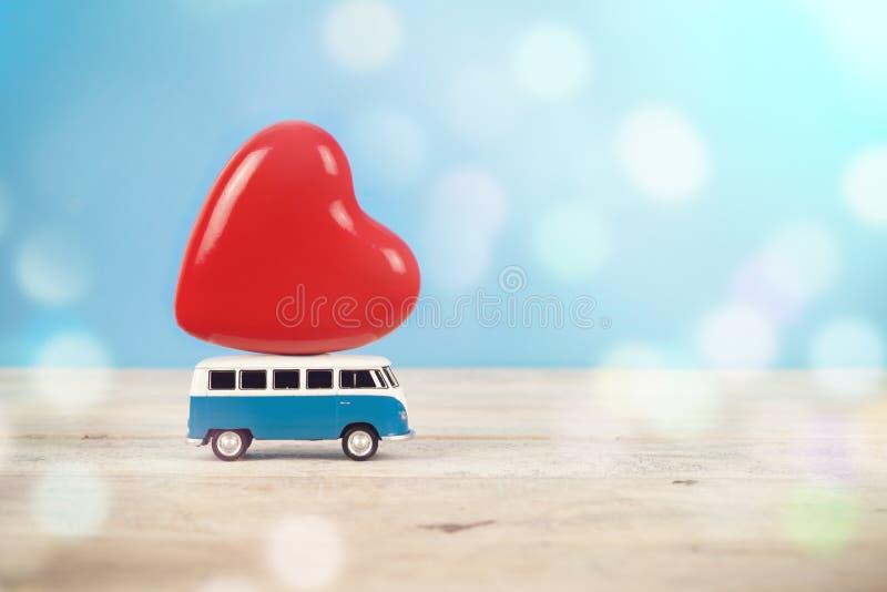 有大红色心脏形象的老葡萄酒玩具搬运车在上面在蓝色bac中 免版税图库摄影