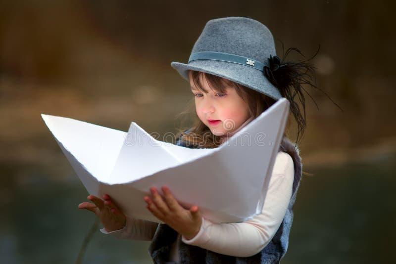 有大纸小船的女孩 库存图片