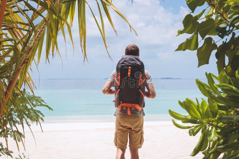 有大背包的年轻人走到在一个热带假日目的地的海滩的 免版税库存照片