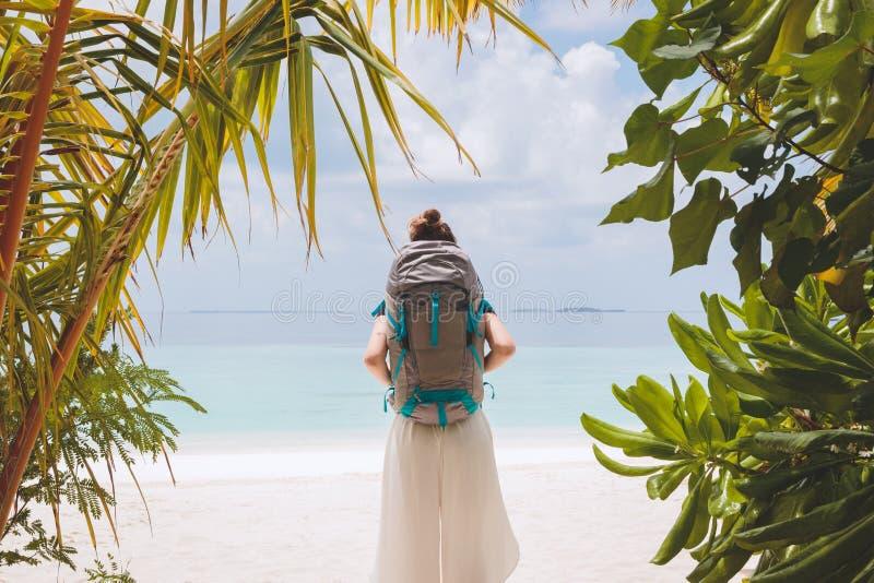 有大背包的年轻女人走到在一个热带假日目的地的海滩的 库存照片