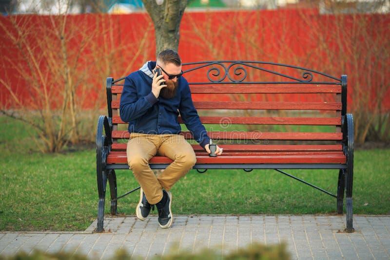 有大胡子的年轻残酷人和在太阳镜的时兴的理发谈话在手机 免版税库存图片