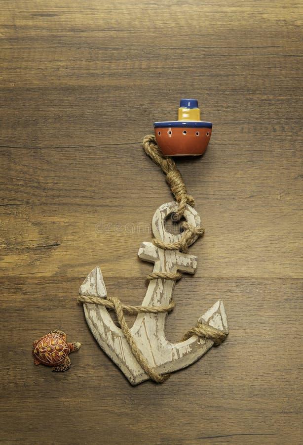 有大船锚和乌龟的小红色船在木桌上 免版税库存图片