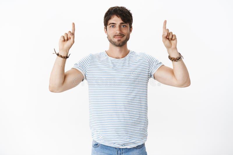 有大蓝眼睛微笑的英俊的年轻,男性人友好用被举的手指向建议的拷贝空间 免版税库存图片